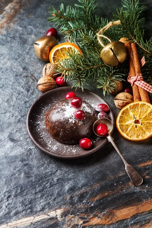 Christmas chocolate pudding with cranberries, walnuts, cinnamon, apples and oranges. Dark background Stock Photo