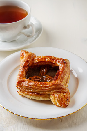 Fresh sweet homemade cinnamon rolls with walnuts on a plate. A cup of hot tea. Swedish cuisine. Light wood background