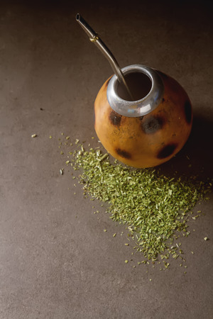 yerba mate: Tradicional de América del Sur té de yerba mate en el círculo calabaza y bombilla. fondo oscuro