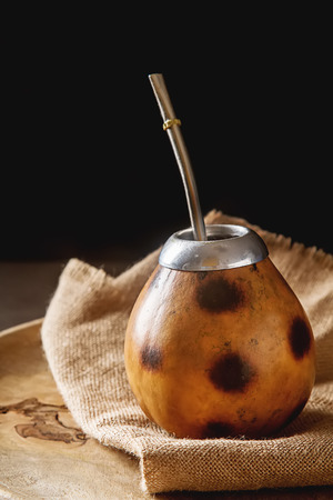 yerba mate: Traditional South American yerba mate tea in the calabash circle and Bombilla. Dark background Foto de archivo