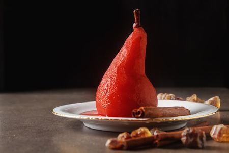 Pears poached in red wine, with star anise on a white plate. Dark background Standard-Bild