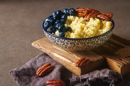 Wheat cereal with blueberries and nuts. Dark gray background Stock Photo