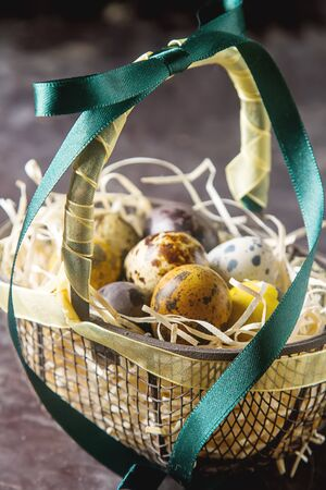 Multi-colored Easter egg. Quail eggs with feathers in basket. Dark background. Spring holiday