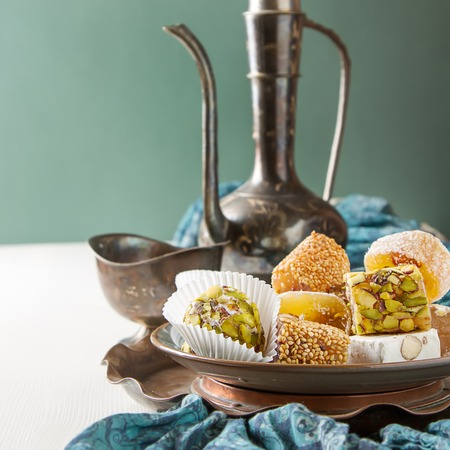Eastern sweets. Turkish delight with pistachios in a vase. The fabric,  white background