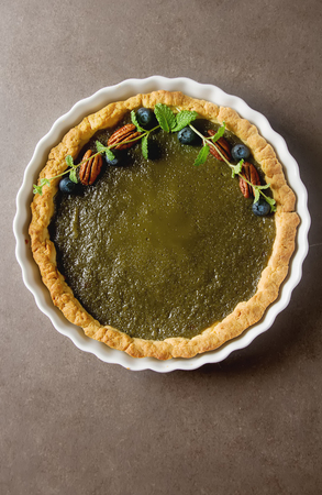 Green tea vegetarian pie match with nuts and mint. Dark background. Selective focus