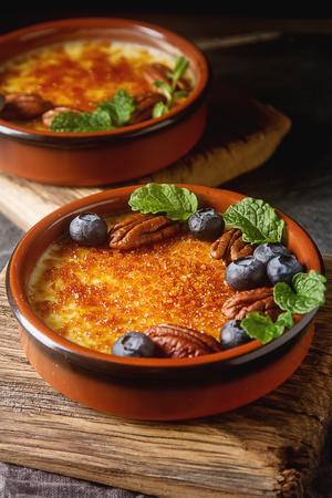 Treditsiozny French dessert. Homemade cream caramel with nuts and berries, mint. Dark background