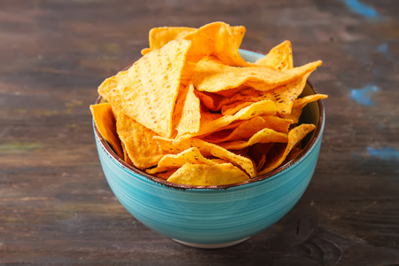 Snack for a party, chips with a tortilla, nachos. Mexican food. Dark background.  Copy space. Stock Photo