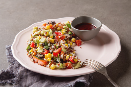 red quinoa: Quinoa salad with corn, tomatoes, avocado, pink sauce on a plate. Gray background Stock Photo
