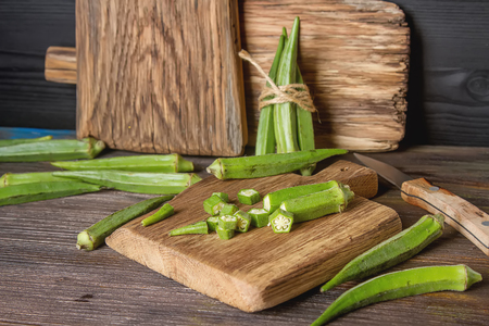 Lady Fingers or Okra over wooden table background. Space for text