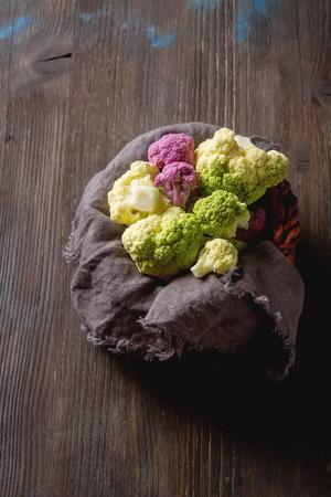 Rainbow of organic cauliflower and Romanesco broccoli on wooden table Stock Photo