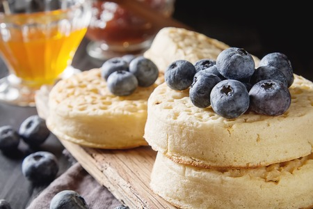 Hot Home made toasted crumpets served with honey, blueberry. Dark wood background. British breakfast Stock Photo