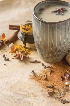 Traditional Indian masala tea in ceramic cup with spices to milk. Wooden batskground