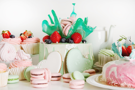 Candy bar with cakes, muffins, meringues, macaroons and biscuits. Pastel shades. Childrens holiday Stock Photo