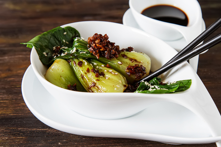 bok choy: Cooked bok choy or chinese cabbage with sesame and  soy sauce. Simple background. Healthy food. Lifestyle