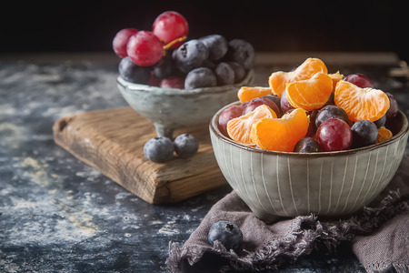 Plate with fruit salad of mandarin, grape, blueberry. Delicious and hearty breakfast options. Dark background Stock Photo