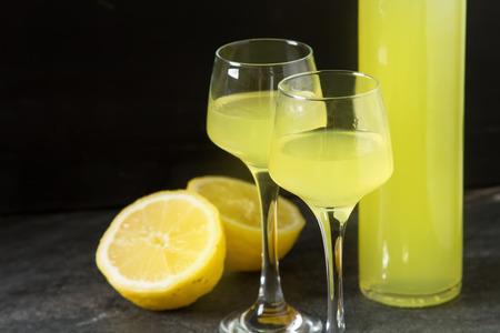 Traditional Italian acoustical leker. Lemonchello of lemons. Dark background