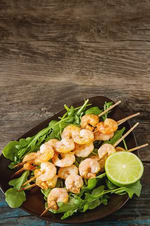 tuna fillet: Mini barbecue with shrimps on a wooden skewer, grill, bbq. Simple background. Healthy food. Lifestyle Stock Photo