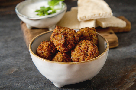 dipping: Middle Eastern traditional dishes. Falafel with sour cream. Vegetarian food Stock Photo