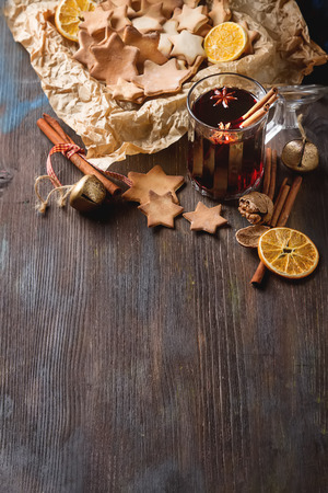 Hot mulled wine in a glass with orange slices, anise and cinnamon sticks, star cookies on vintage wood table. Christmas or winter warming drink with recipe ingredients around