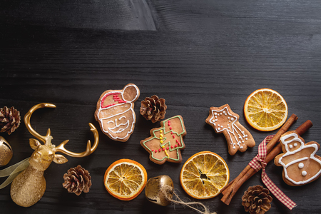 gingerbread man: Merry christmas holiday decoration background with ginger man snowflakes snowman and tree cookies dry orange. Dark wooden table. Space for text
