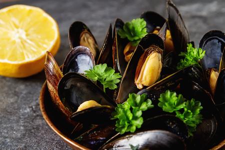 Moules aux herbes dans un bol en cuivre. Fruit de mer. Nourriture au bord de la mer française. Fond sombre Banque d'images