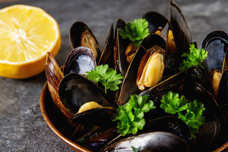Mussels with herbs in a copper bowl. Seafood. Food at the shore of the French Sea. Dark background Stok Fotoğraf - 82722582