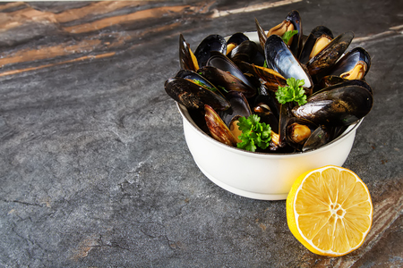 Mussels with herbs in a white bowl with lemon. Seafood. Food at the shore of the French Sea. Dark background