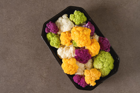 romanesco: A rainbow of food. Purple cauliflower, orange cauliflower and broccoli, from the local market in London. Food for a vegan and a vegetarian. Dark background
