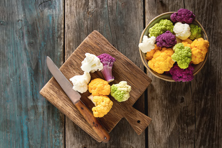 A rainbow of food. Purple cauliflower, orange cauliflower and broccoli, from the local market in London. Food for a vegan and a vegetarian. Dark background
