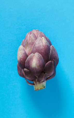 Baby ripping organic Artichokes. Food for a vegan and a vegetarian. Diet, food concept. Multicolored background Stock Photo