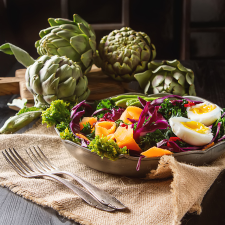 Fresh vegetarian salad with cabbage kale broccoli carrot egg avocado and artichokes on a gray metal plate, napkin. Dark wood background