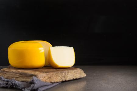 Round gouda cheese. Dark background Фото со стока