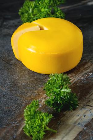 Round gouda cheese with parsley. Dark background Stock Photo