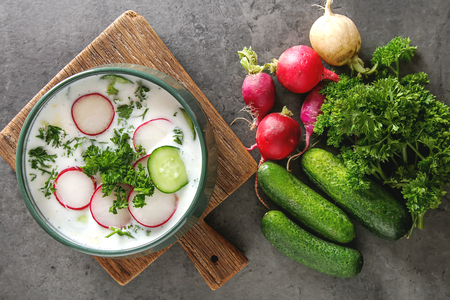 Summer cold soup - okroshka in a ceramic bowl. Ingredients of potatoes, radishes, cucumbers, parsley, eggs. Dark background