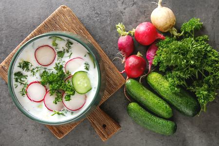 Sopa fría de verano - Okroshka en un tazón de cerámica. Ingredientes de patatas, rábanos, pepinos, perejil, huevos. Fondo oscuro Foto de archivo