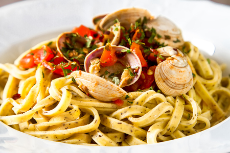 Italian tagliatelle in a restaurant with mussels and tomatoes. Dark background