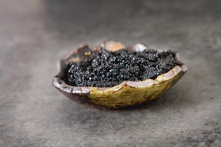 Black sturgeon caviar in a ceramic bowl. Dark background