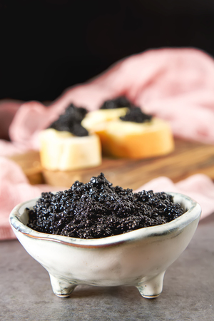 Sandwich with caviar of black sturgeon and white bread. Dark background Stock Photo