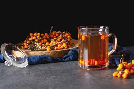 Autumn meal. Sea buckthorn tea. Dark background Stock Photo