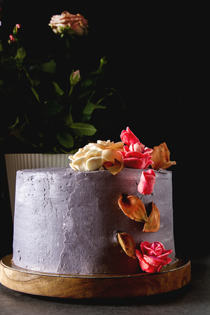 Chocolate cake with flowers for birthday. Dark background