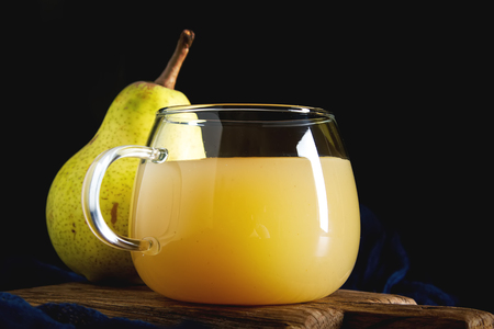 Pear grog or cider in autumn leaves with cinnamon. Dark background