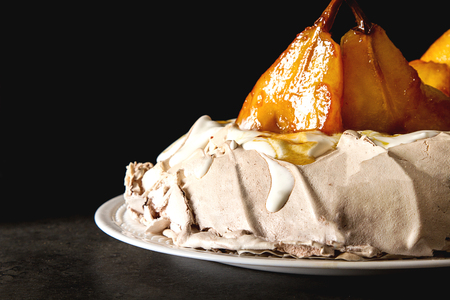 A traditional Pavlov dessert with pears and white cream. French cuisine. Dark background