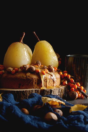 Autumn meal. Pie with pears, sea buckthorn and nuts. Dark background