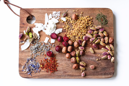 Dried fruits. nuts fistaski, spices on a wooden board. Light background
