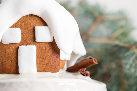 New Year cake with Christmas trees and gingerbread houses and cinnamon. Light background