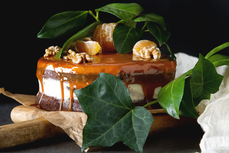 Chocolate cake with white cream and caramel sauce. Dark background. Birthday