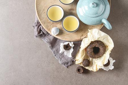 Porcelain chinese cups, steel teaspoon. Black, green, puerh, oolong, tieguanyin, sencha, tea. Gray background Standard-Bild
