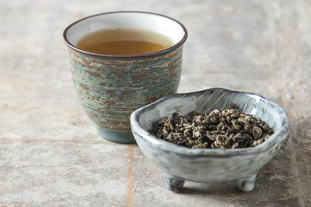 Porcelain chinese cups, steel teaspoon. Black, green, puerh, oolong, tieguanyin, sencha, tea. Gray background Stock Photo