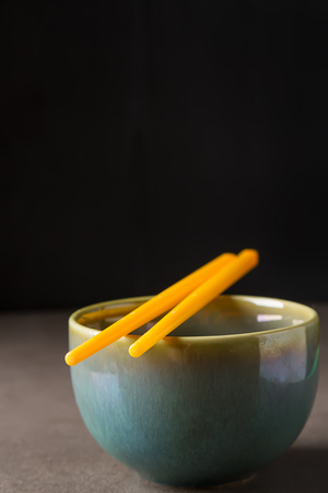 Chinese food. Two chopsticks for eating. Food sticks. Dark background Stock Photo