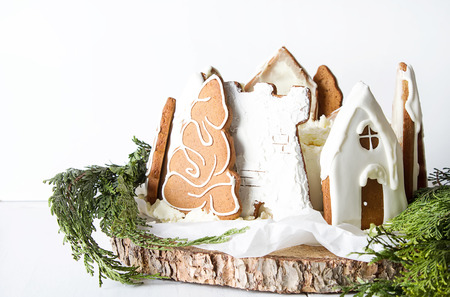 Cake decorated with houses from Ginger honey cakes. Christmas tale. White background Stock Photo
